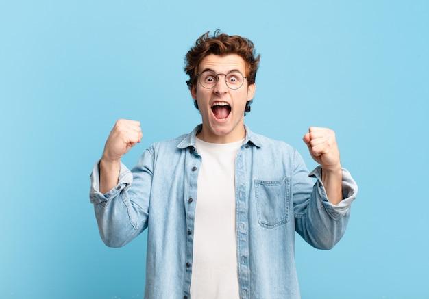 Jonge knappe jongen die agressief schreeuwt met een boze uitdrukking of met gebalde vuisten om succes te vieren