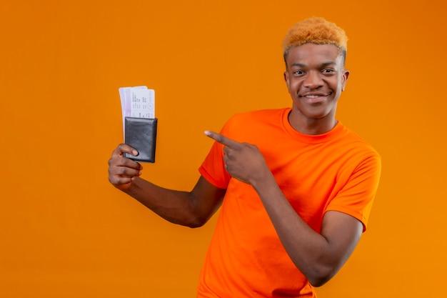 Jonge knappe jongen die een oranje t-shirt draagt en een vliegticket houdt naar het met een vinger glimlachend zelfverzekerd staande over oranje muur
