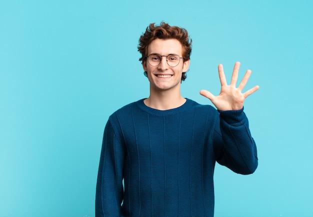 Jonge knappe jongen die lacht en er vriendelijk uitziet, nummer vijf of vijfde toont met de hand naar voren, aftellend