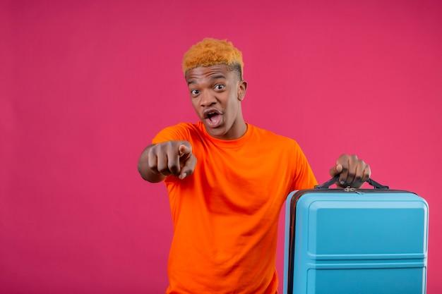 Jonge knappe jongen die oranje de reiskoffer van de t-shirtholding draagt ?? die met vinger naar camera richt die verbaasd en verbaasd over roze muur kijkt