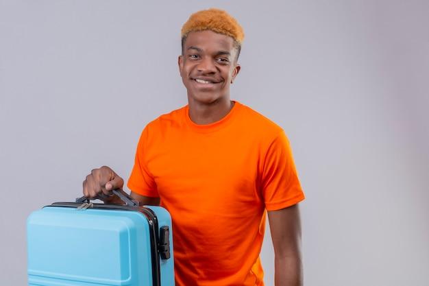 Jonge knappe jongen die oranje de reiskoffer van de t-shirtholding draagt die positief en gelukkig status over witte muur glimlacht
