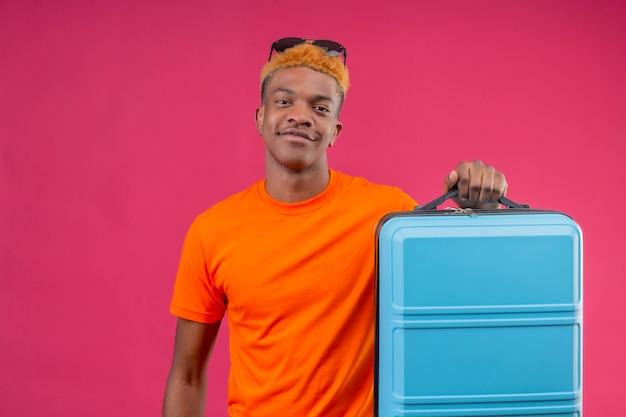 Jonge knappe jongen die oranje de reiskoffer van de t-shirtholding draagt die zelfverzekerd over roze muur glimlacht