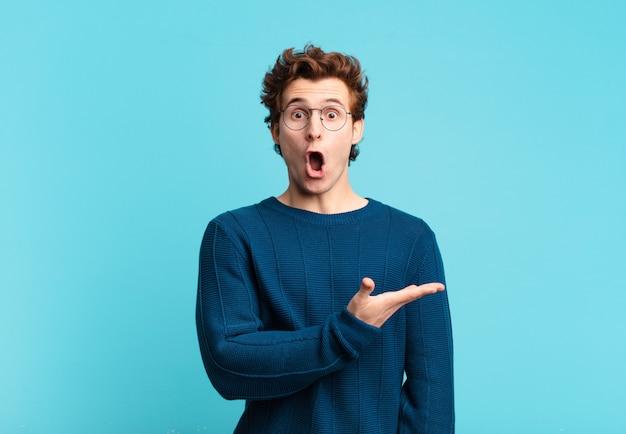 Jonge knappe jongen die verrast en geschokt kijkt, met open mond terwijl hij een object vasthoudt met een open hand aan de zijkant