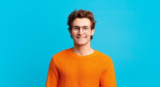 Jonge knappe jongen die vrolijk lacht, zich gelukkig voelt en een concept in kopieerruimte laat zien met handpalm