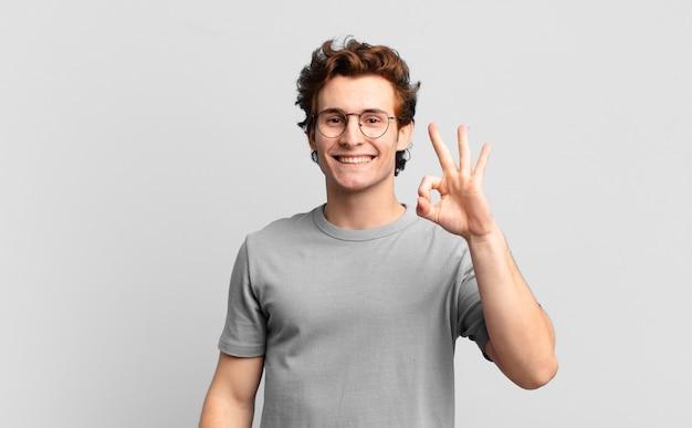 Jonge knappe jongen die zich gelukkig, ontspannen en tevreden voelt, goedkeuring toont met een goed gebaar, glimlachend