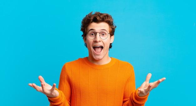 Jonge knappe jongen die zich gelukkig, opgewonden, verrast of geschokt voelt, glimlacht en verbaasd over iets ongelooflijks