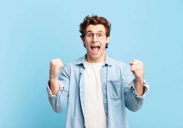 Jonge knappe jongen die zich geschokt, opgewonden en gelukkig voelt, lacht en succes viert, en zegt wow!
