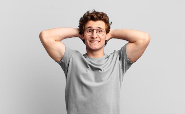 Jonge knappe jongen die zich gestrest, bezorgd, angstig of bang voelt, met de handen op het hoofd, in paniek bij vergissing