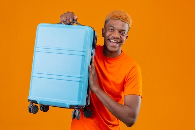 Jonge knappe jongen draagt ?? oranje t-shirt met reiskoffer glimlachend vrolijk positief en gelukkig staande over oranje muur