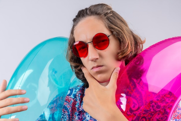 Jonge knappe jongen dragen rode zonnebril houden kleurrijke opblaasbare ringen camera kijken met peinzende verdachte uitdrukking met hand op kin denken staande op witte achtergrond