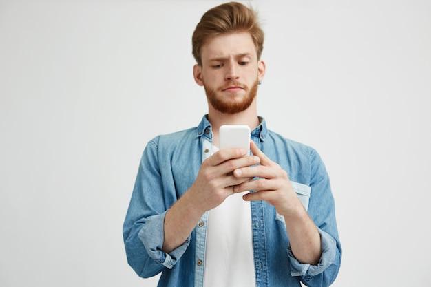 Jonge knappe jongen fronsen kijken naar telefoonscherm surfen op internet.