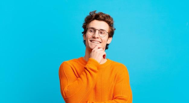 Jonge knappe jongen glimlachend met een gelukkige, zelfverzekerde uitdrukking met de hand op de kin, zich afvragend en opzij kijkend