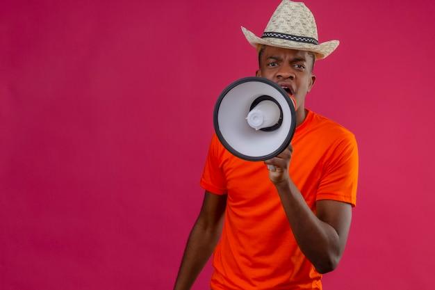 Jonge knappe jongen in zomerhoed die een oranje t-shirt draagt die naar megafoon schreeuwt met een boze uitdrukking die zich over roze muur bevindt