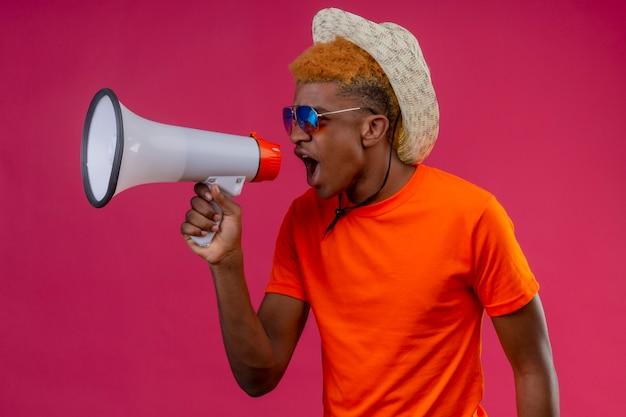 Jonge knappe jongen in zomerhoed die oranje t-shirt draagt die aan megafoon schreeuwt
