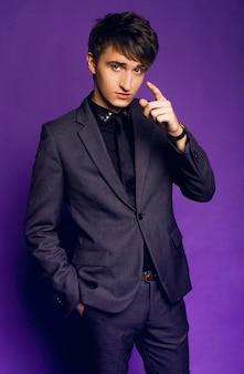 Jonge knappe jongen poseren in studio in stijlvol grijs pak, zakenman stijl, violet paarse studio achtergrond.