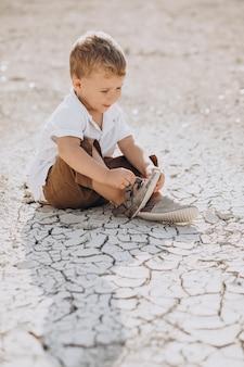 Jonge knappe jongen zittend op de grond