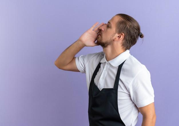 Jonge knappe kapper dragen uniforme hand in de buurt van mond bellen iemand met gesloten ogen geïsoleerd op paarse achtergrond met kopie ruimte
