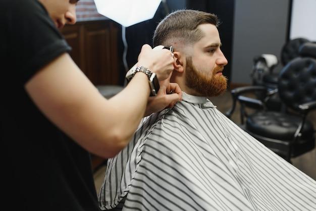 Jonge knappe kapper maken van kapsel van aantrekkelijke bebaarde man in de kapsalon