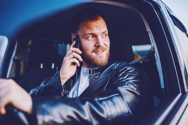 Jonge knappe kaukasische bebaarde blonde man in leren jas zijn auto rijden en het gebruik van slimme telefoon.