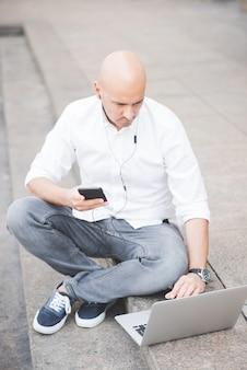Jonge knappe kaukasische kale bedrijfsmensenzitting op een trap die laptop met behulp van