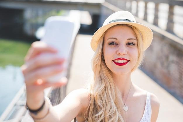 Jonge knappe kaukasische lange blonde rechte haarvrouw die technologische apparaten gebruiken