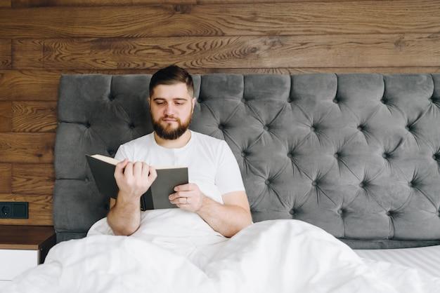 Jonge knappe kaukasische mens die een boekzitting in bed leest
