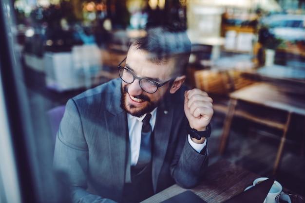 Jonge knappe kaukasische modieuze bebaarde lachende zakenman in pak en met bril zitten in café en op zoek via venster.