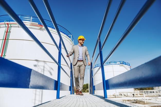 Jonge knappe kaukasische zakenman in pak en met helm op hoofd lopen op brug en kijken naar zijn raffinaderij.