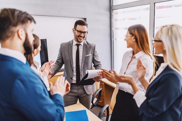 Jonge knappe kaukasische zakenman permanent in boardroom met zijn collega's.