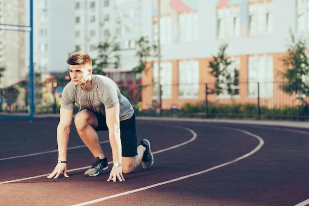 Jonge knappe kerel bij sport in de ochtend op stadion. hij draagt sportkleding en luistert naar muziek via een koptelefoon. hij begint te rennen.