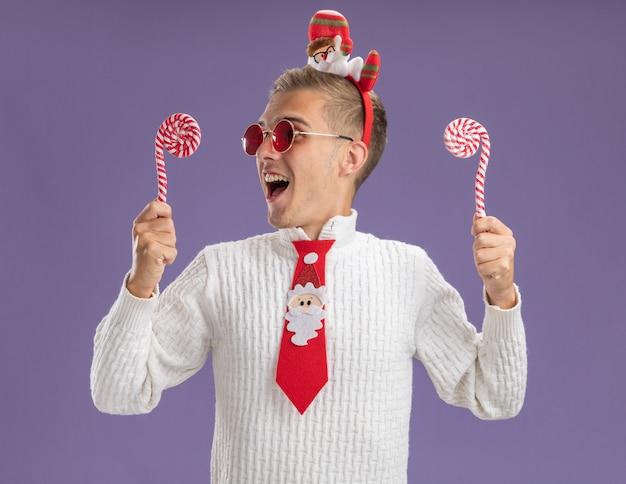 Jonge knappe kerel die de hoofdband en de stropdas van de kerstman draagt ?? met kerst zuurstokken kijken naar een van hen klaar om te eten geïsoleerd op paarse achtergrond