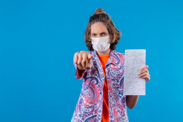 Jonge knappe kerel die een beschermend gezichtsmasker draagt die kaart toont die naar camera boos en woedend met u wijst die over blauwe achtergrond staat