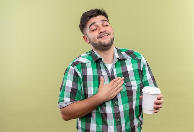 Jonge knappe kerel die een geruit overhemd draagt dat naar zichzelf wijst en plastic koffiekop houdt die zich over kaki muur bevindt