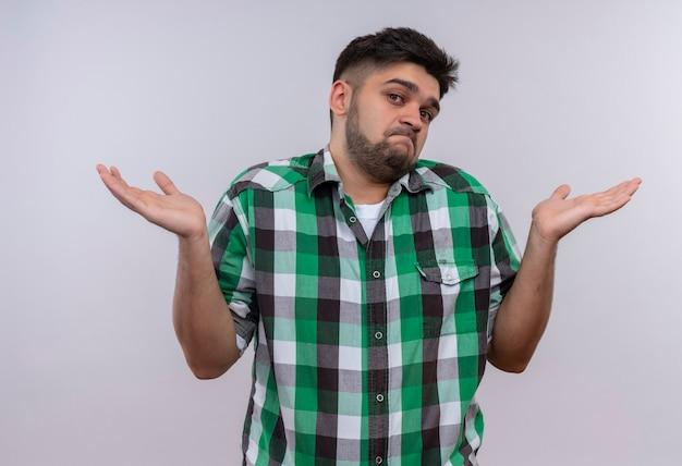Jonge knappe kerel die een geruit overhemd draagt dat onbeslist over witte muur kijkt