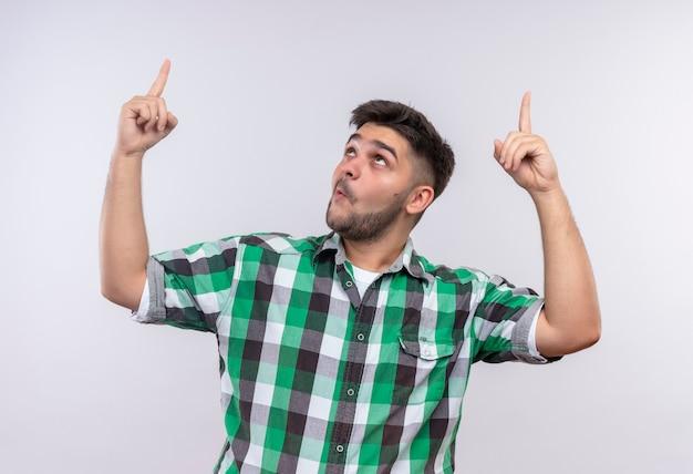 Jonge knappe kerel die een geruit overhemd draagt dat verrast met wijsvinger benadrukt die zich over witte muur bevindt