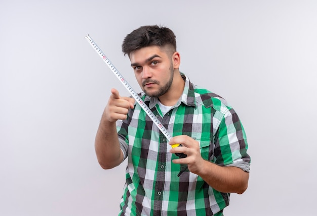 Jonge knappe kerel die een geruit overhemd draagt dat zich meetinstrument houdt die over witte muur richt