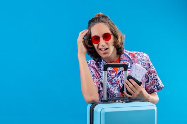 Jonge knappe kerel die een rode zonnebril draagt met een reiskoffer die vliegtickets houdt en kijkt verward met de hand op het hoofd voor een fout van de fout die zich over de blauwe achtergrond bevindt