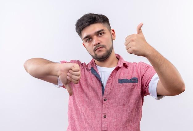 Jonge knappe kerel die een roze poloshirt draagt, onbeslist kijkend met gelukkige en ongelukkige duimen die zich over witte muur bevinden