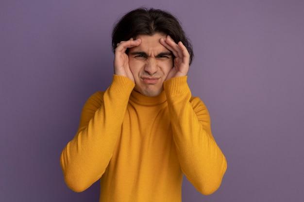 Jonge knappe kerel die gele coltrui draagt ?? die handen rond ogen zet die op purpere muur worden geïsoleerd
