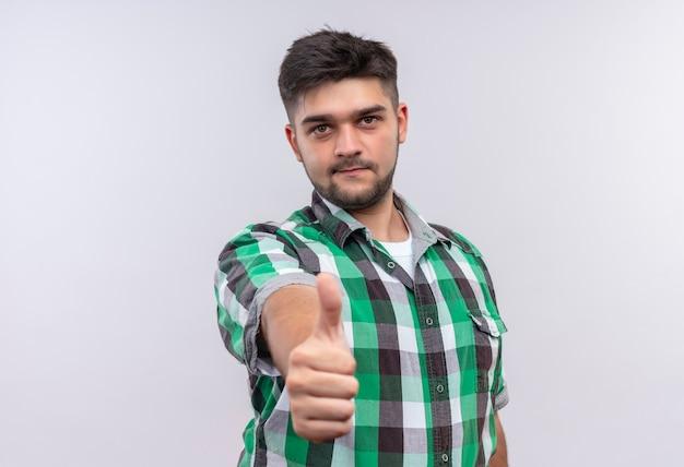 Jonge knappe kerel die geruit overhemd draagt dat als teken doet dat zich over witte muur bevindt