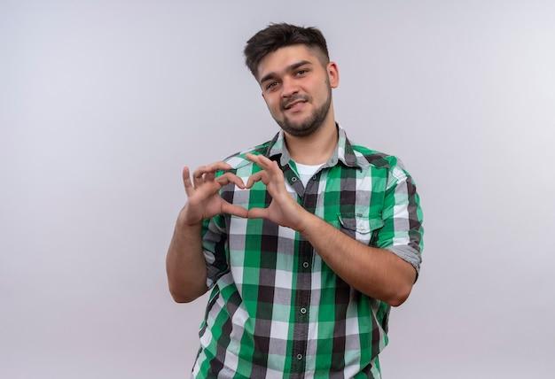 Jonge knappe kerel die geruit overhemd draagt dat liefdeteken met handen draagt die zich over witte muur bevinden
