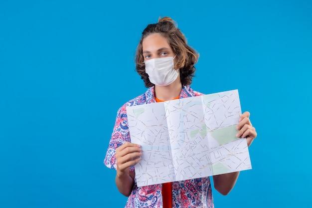 Jonge knappe kerel die gezichts beschermend masker draagt dat kaart met ernstige zekere uitdrukking op gezicht toont die zich over blauwe achtergrond bevindt