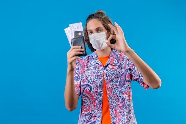 Jonge knappe kerel die gezichts beschermend masker draagt dat luchtkaartjes houdt die ok teken doen kijken met zelfverzekerde uitdrukking die zich over blauwe achtergrond bevindt