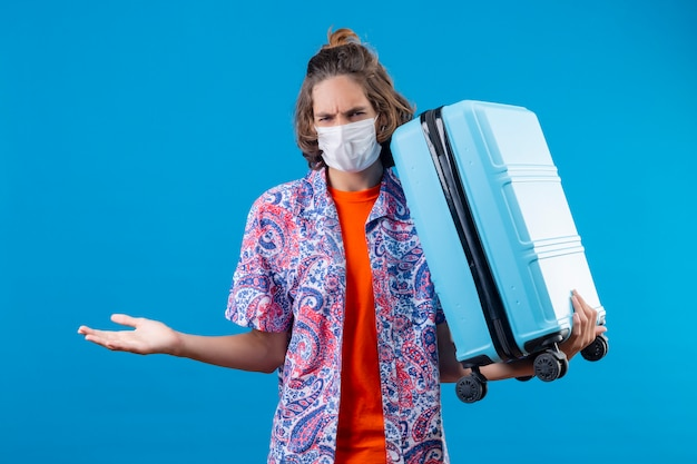 Jonge knappe kerel die gezichts beschermend masker dragen die reiskoffer houden die camera bekijken met fronsend gezicht die gebaar met hand maken als het stellen van een vraag status