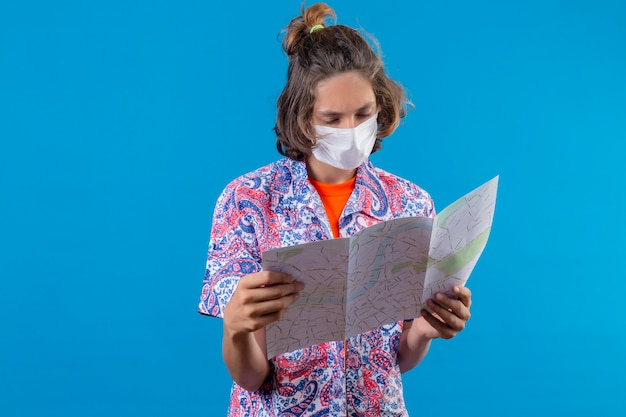 Jonge knappe kerel die gezichtsbeschermend masker draagt dat kaart houdt en met ernstig gezicht bekijkt dat zich over blauwe achtergrond bevindt