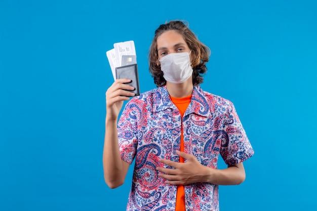 Jonge knappe kerel die gezichtsbeschermend masker draagt dat luchtkaartjes houdt die met zelfverzekerde uitdrukking over blauwe achtergrond kijken
