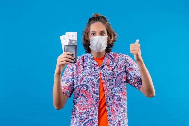 Jonge knappe kerel die gezichtsbeschermend masker draagt dat luchtkaartjes houdt die verbaasd op zoek zijn naar duimen glimlachend vrolijk permanent over blauwe achtergrond