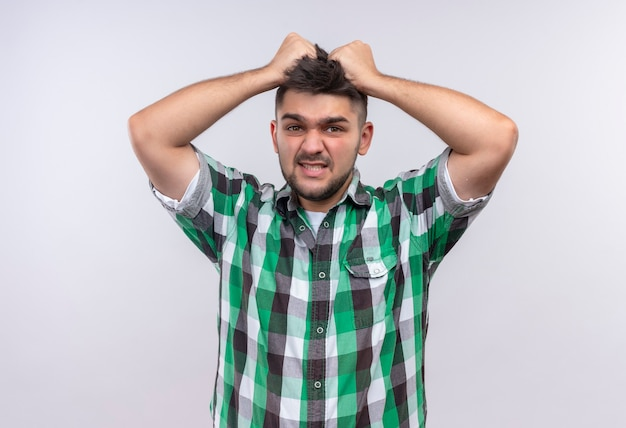 Jonge knappe kerel die het geruite hoofd van de overhemdsholding draagt die beu staande over witte muur kijkt