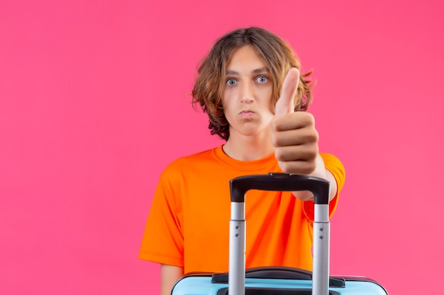 Jonge knappe kerel die in oranje de reiskoffer van de t-shirtholding camera bekijkt verbaasd toont duimen omhoog die zich over roze achtergrond bevinden