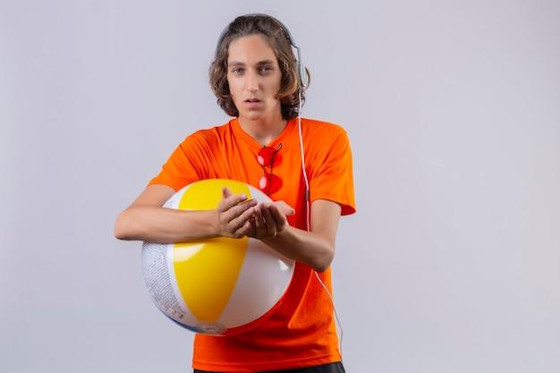 Jonge knappe kerel die in oranje t-shirt opblaasbare bal met hoofdtelefoons houden die gesturing met handen die wapens bij elkaar houden die ongelukkige status kijken